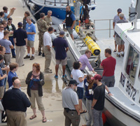 The attendees stand on the pier next to the Meriel R. loaded with the AUV.