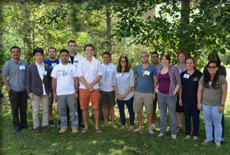 Group photo of 16 new students standing on the grass under green leafy trees.
