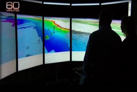 Black silhouettes of Larry and 60 Minutes host against the large panel display of Alaskan bathymetry.
