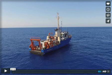 Still from the video showing an aerial shot of a research vessel at sea.