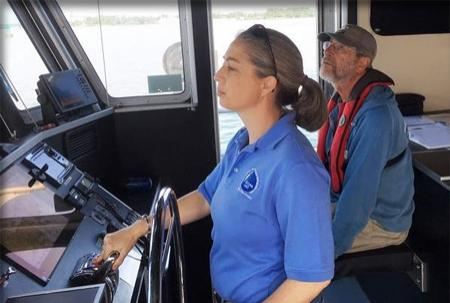 Capt. Emily at the wheel inside the cabin of the Gulf Surveyor; First Mate Paul sits nearby.