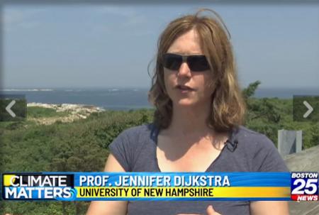 Jenn Djikstra in sunglasses talking with coast and ocean in the background.