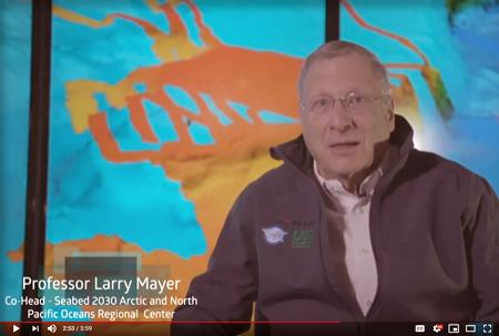 Larry Mayer speaking with a bathymetric image on a screen behind him.