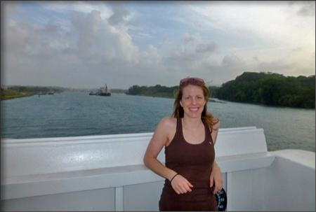 Lindsay McKenna standing with her back to the ship's rail with the entrance to the Panama Canal in the distance.