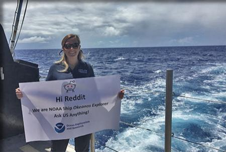 "Meme on the aft deck of the Okeanos Explorer holding sign that says, ""Ask Us Anything."""