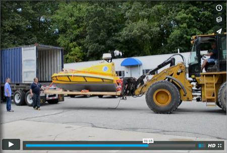Big yellow construction vehicle with the yellow ASV on its front skids.