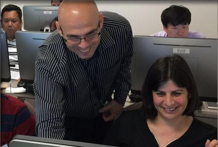 Dr. Shachak Pe'eri leans over a students work station to show her something on the monitor.