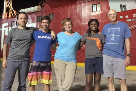 The survey team poses on the pier in front of the M/V Fugro Supporter.